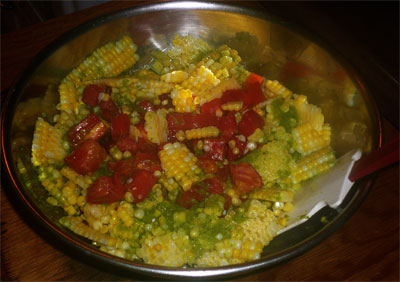 Mixing corn, tomatoes and vinaigrette